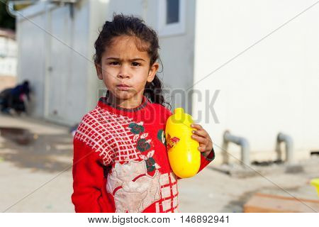 ZAGREB, CROATIA - OCTOBER 21, 2013: Cute little Roma girl playing with soap and water on street.