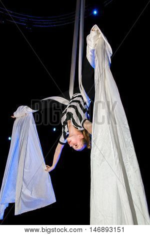 A blond teenage aerialist performs an upside down straddleback butterfly on stage during rehearsal. Stage lights add a bit of color and drama.