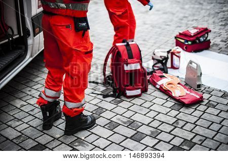 emergency volunteer operators with medical devices and emergency bags and rucksacks during an accident