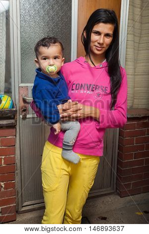 ZAGREB, CROATIA - OCTOBER 21, 2013: Roma mother holding baby in front of their house.