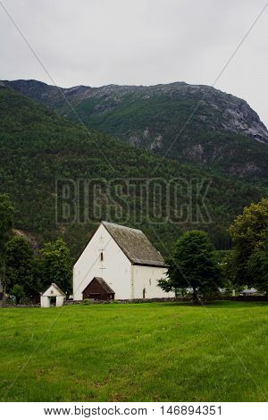 Norway. Church in the mountains. Church and cemetery in Norway. Mown meadow. White house.