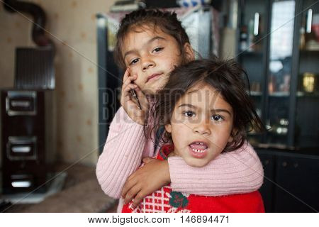 ZAGREB, CROATIA - OCTOBER 21, 2013: Portrait of little Roma girl hugging her sister and holding mobile phone.