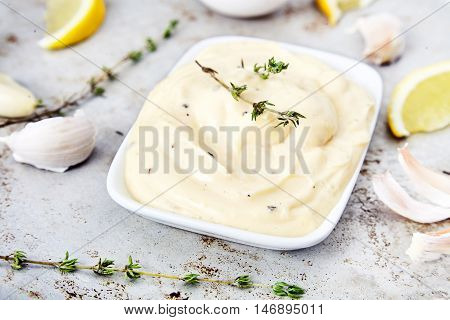 Delicious homemade hollandaise or mayonnaise sauce from butter, oil, lemon juice, water, salt, eggs with garlic and thyme. Gravy boat on a metal back, lemon slices, eggs, garlic and thyme sprigs