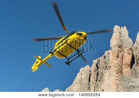 Medical rescue helicopter flying rescue injured climber on the Tre Cime. Italy, Dolomites