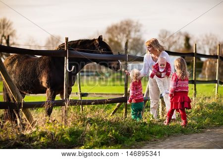 Family on a farm in autumn. Mother and kids feed a horse. Outdoor fun for parents and children. Woman with baby and toddler playing with pets. Child feeding animal on a ranch on cold fall day.