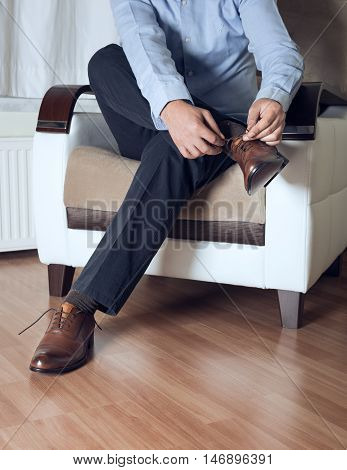 Man ties his brown shoes high quality and high resolution studio shoot