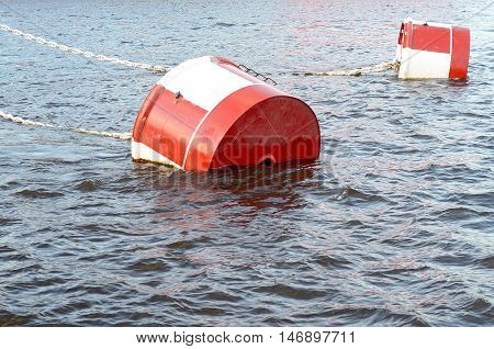 Red and white metal mooring buoys. White anchor chain. River water surface.
