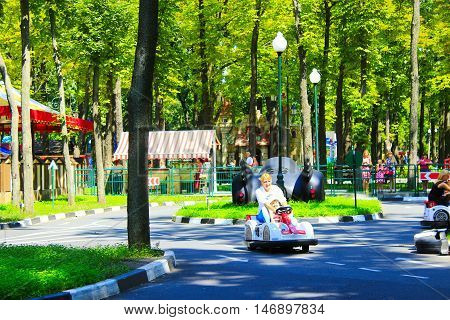 Kharkiv / Ukraine. 07 August 2016: children with their parents drive the electric cars in Gorky park in Kharkiv.  07 August 2016 in Kharkiv / Ukraine.