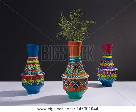 Still life of three artistic painted colorful handcrafted pottery vases and little green branches with harsh shadow on white table and black wall