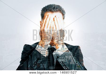Stressed businessman covering face with hands on abstract city background. Double exposure