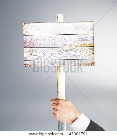 Businessman hand holding empty wooden signboard on grey background. Mock up 3D Rendering