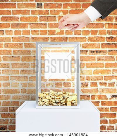 Businessman hand putting coin into donation box with blank label. Red brick wall background. Charity concept. Mock up 3D Rendering