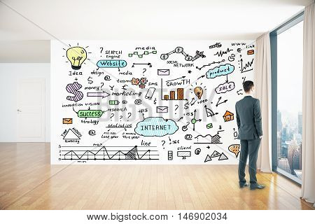 Young businessman looking out of window in interior with colorful business drawings on wall. Success concept. 3D Rendering