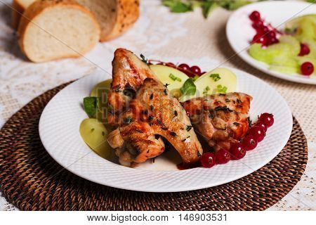 chicken wings with potatoes and cranberries on the plate still life in the restaurant Still restaurant house thyme