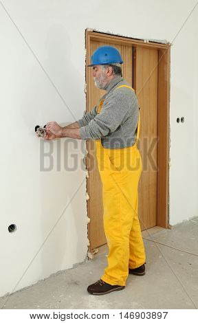 Electrician At Construction Site Install Electrical Plug