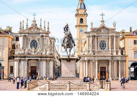 Turin, Italy - June 12, 2016: People walk on San Carlo square with Santa Cristina, San Carlo Borromeo churches and monument in the old city center of Turin in Italy
