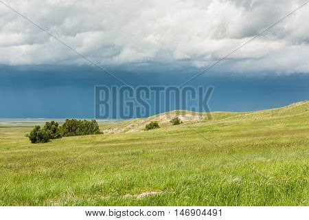 Dark blue rain storm clouds contrast with green prairie steppe grass valley in Badlands National Park