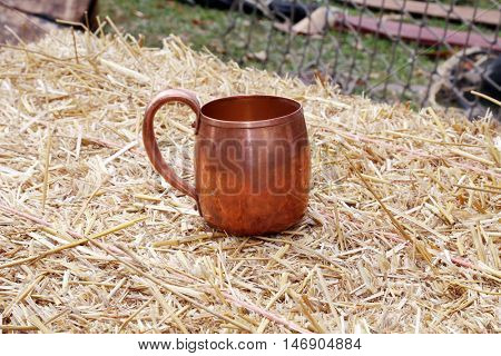 Antique copper cup on a bail of hay outdoors