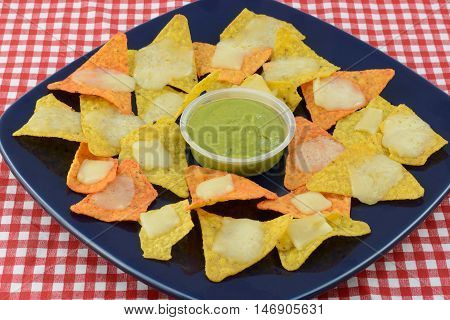 Nachos with tortilla chips, mozzarella cheese and guacamole dip on blue plate