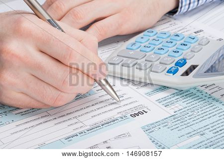 A Man Filling Out Usa Tax 1040 Form With Dollars And Calculator Neat It