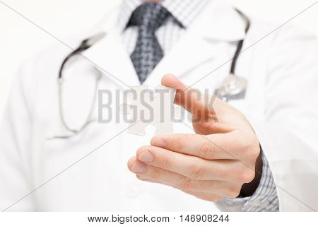 Doctor Holding Two Pieces Of Puzzle In His Hands - Close Up Studio Shot