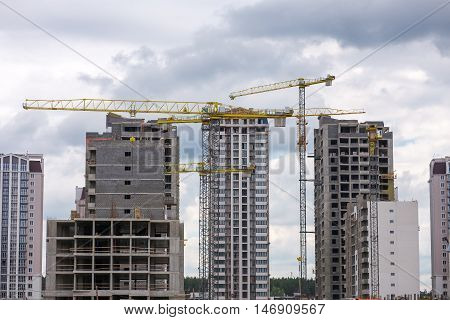 Building Construction with Cranes. Construction of multi-storey buildings. Workers work on building object.