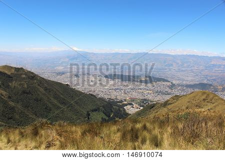 This photo shows a view of the valley of the Quito City from west to east and the Cayambe Volcano in the background at Quito, Ecuador.