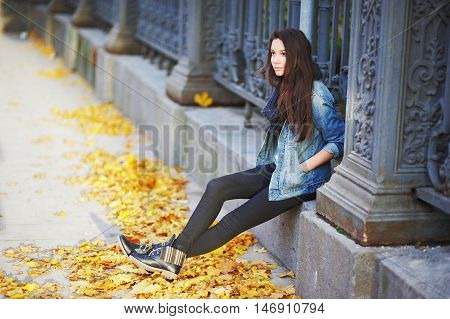 Young pretty woman sitting pensively on a stone slab a beautiful iron fence with his hands in the pockets of a denim jacket around the yellow autumn leaves of maple.