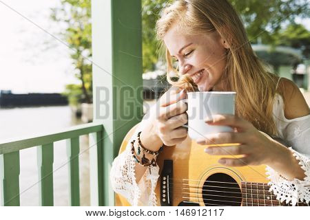 Blonde Girl Holding A Cup And Guitar By The Porch Concept
