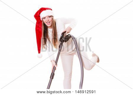 Woman vacuuming the house. Funny girl in santa helper hat with vacuum cleaner. Christmas time and housework concept.
