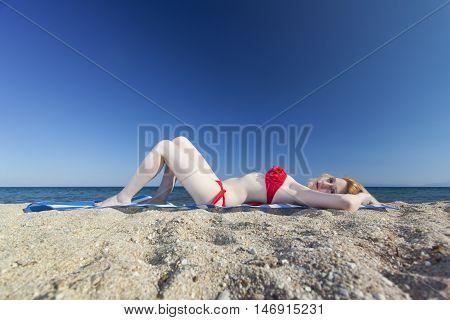 woman lying on a beach in summer
