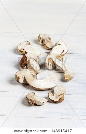 heap of raw porcino mushrooms on white wood