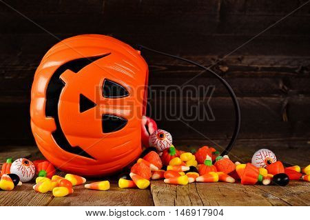Halloween Jack O Lantern Candy Holder With Spilling Candy On Rustic Wood Background