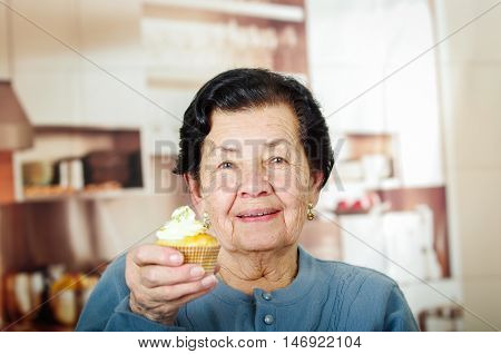 Older hispanic happy woman wearing blue sweater sitting in front of camera showing off cupcake with cream topping.