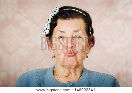 Older cute hispanic woman wearing blue sweater and polka dot bowtie on head making kiss lips for the camera.