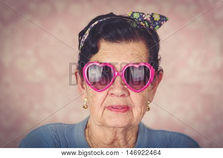 Older cool hispanic woman wearing blue sweater, flower pattern bow on head and pink heartshaped sunglasses looking into camera.