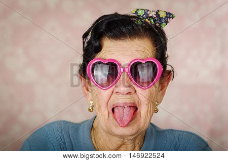 Older cool hispanic woman wearing blue sweater, flower pattern bow on head and pink heartshaped sunglasses looking into camera showing her tongue.