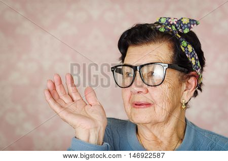 Older hispanic cute woman with flower pattern bow on her head wearing blue sweater and black large framed glasses looking to the side of camera smiling one hand raised.
