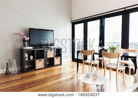 Modern apartment living room with tv on buffet and bi fold door to balcony