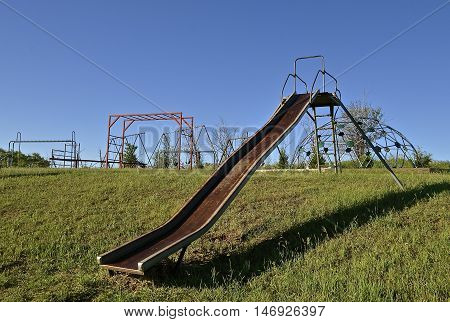 Old metal slippery slide located on a a hill with swing sets in the background