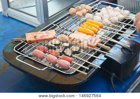 Grilling sausages on the electronic grill Different sauasges and hotdog