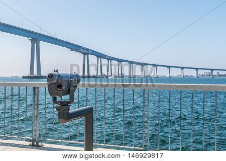 Sightseeing binoculars facing the Coronado bridge in San Diego, California, on a viewing pier at Cesar Chavez Park.
