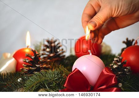 Hand with a match and second advent candle.