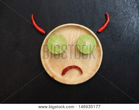 Feeling concept. Devil angry wooden plate is face lemon slice is eye red dried chilli is mouth and red chilli horn