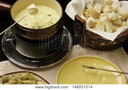 Cheese fondue - a piece of bread croutons in a liquid cheese
