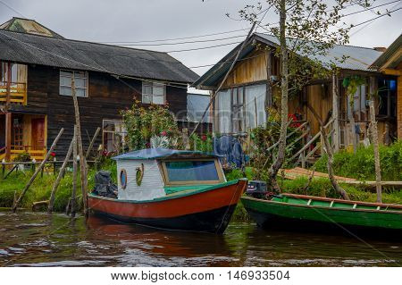 PASTO, COLOMBIA - JULY 3, 2016: small boat parked infront of some colorfull houses in la cocha lake.