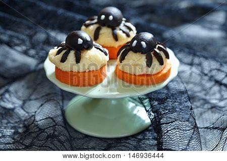 Halloween Appetizer. Olive spider on carrot and cheese ball