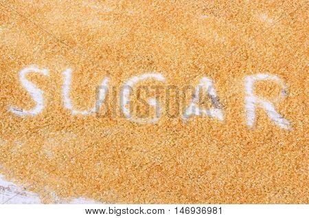 Word sugar written in granulated natural brown cane sugar
