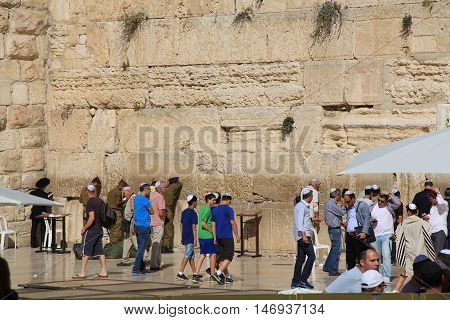 JERUSALEM, ISRAEL, OCTOBER 24, 2013, Young Jewish boys along with other worshipers praying at the mens side of the Western Wailing Wall which is also known as the Kotel, the most holy site for Jews in Jerusalem, Israel.