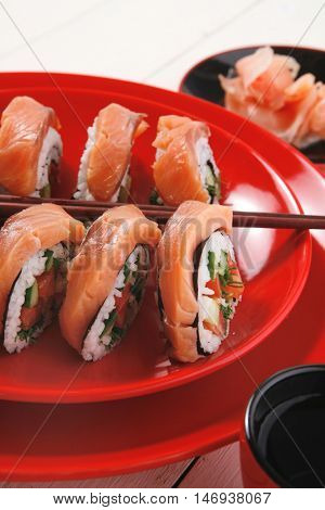 japanese cuisine onigiri sashimi inside out sushi rolls with ginger and sake cup on red plate over white wooden table